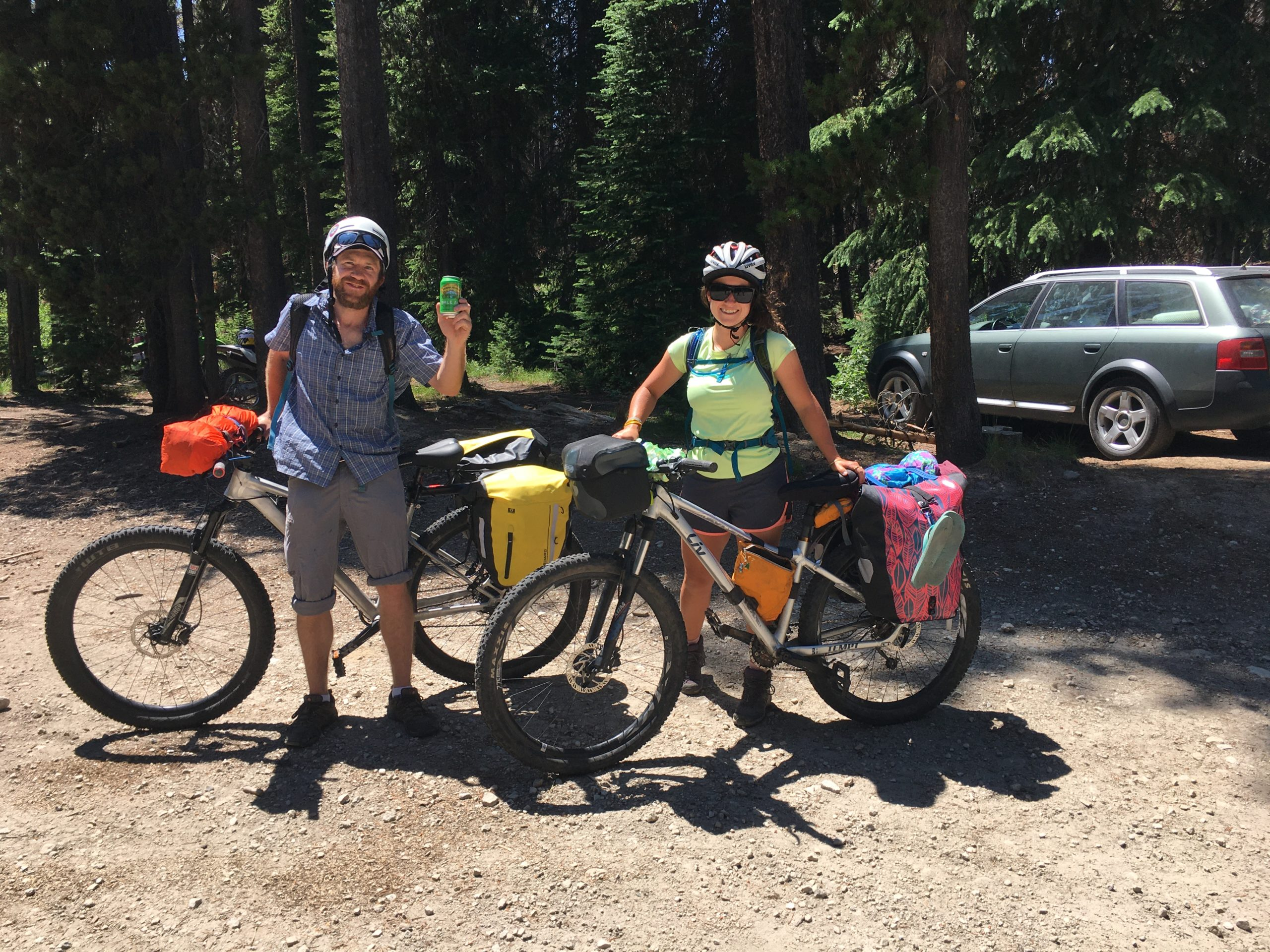 Rochelle and her partner Rob pose in front of their packed up bikes on the side of the road. Rob is holding up a can and cheering in the photo.